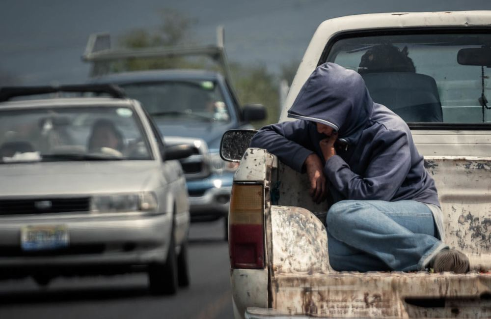 A field worker, likely for Driscoll's Berries, rides in the back of a truck in Jocotopec, Jalisco, Mexico.