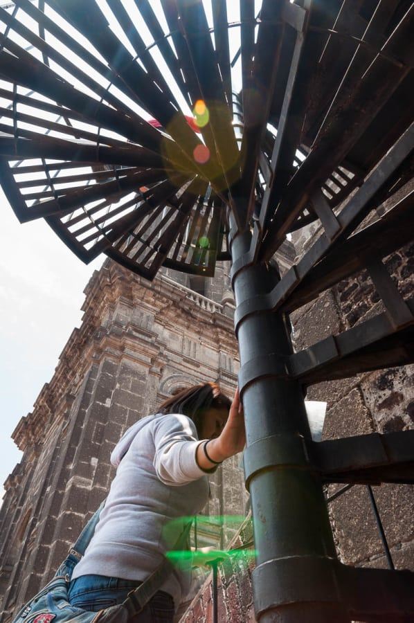 A woman walks up the staircase to get to the roof the Metropolitan Cathedral in Mexico City.