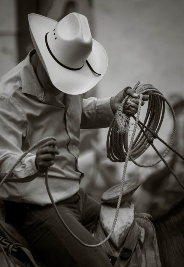 A cowboy practices his roping skills in the bullring.