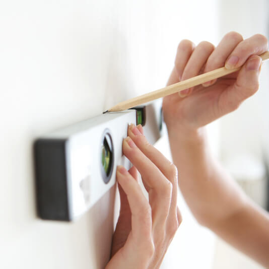 Ask someone to hold your picture frame in position against the wall and then draw a light mark along the top centre of the picture, and use a spirit level to make sure it's straight. You can use this line as a guide when you're ready to hang the picture.