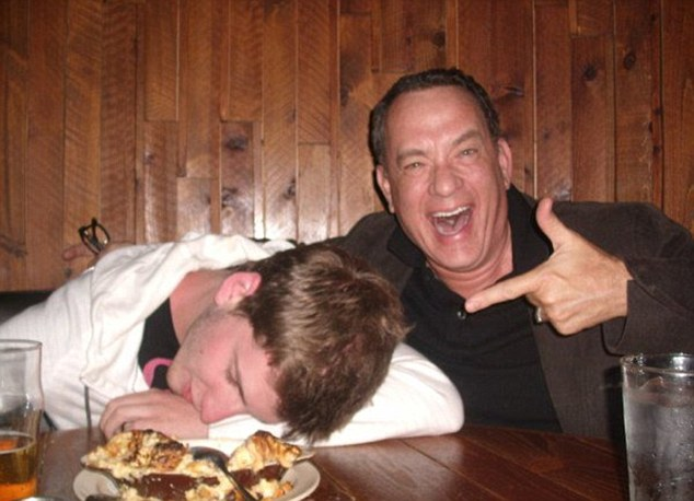 So two guys go into a bar: Tom Hanks hams it up for the camera with a fan in North Dakota last week