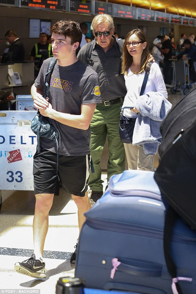 Loving couple: Harrison gently put his arm around the shoulders of his 52-year-old wife of seven years as they arrived at the airport