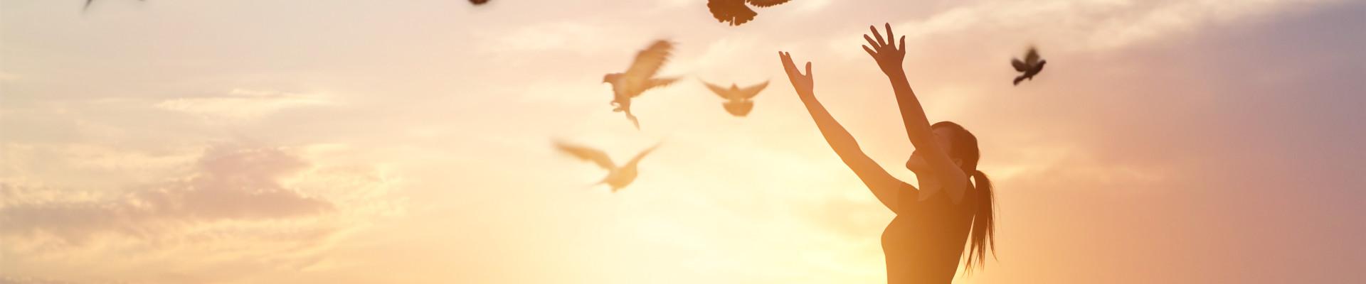 women releasing doves sunset