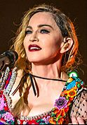 A woman with plaited hair, blue eyes and red lipstick wearing a colorful dress and guitar strap.