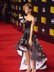 Rihanna standing on a red carpet in an elaborate dress