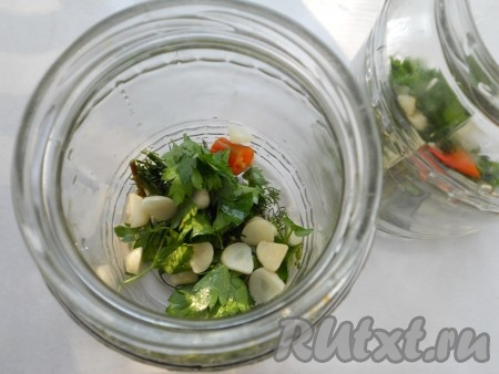 Зелень укропа и петрушки измельчить, чеснок порезать кусочками. Выложить на дно чистых, сухих банок. Добавить по кусочку острого перца. Масло растительное прокалить и влить в банки (по 1 столовой ложке).
