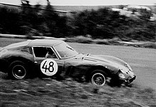 Black and white photo of a sports car number 48 driving left to right, foreground speed-blurred