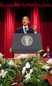 """President Obama stands at a podium delivering a speech on """"A New Beginning"""" at Cairo University on June 4, 2009"""