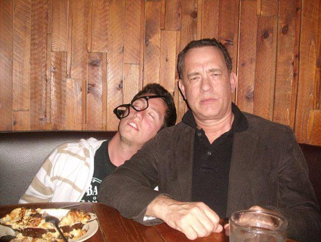 Prank partners: Hanks does his best wasted face as his fan pretends to slump drunkenly against him