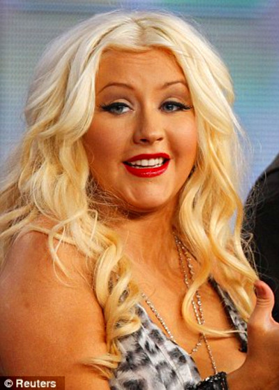 Christina Aguilera answers a question as Blake Shelton and Adam Levine ...