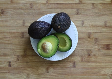 avocados on a white plate on a wooden table Credit: ponce_photography at Pixabay.com