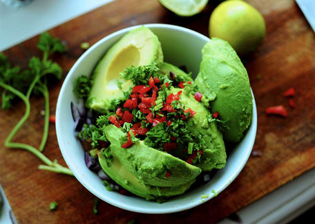 avocados cut in half with minced red bell peppers onions and cilantro in a white bowl on a wooden cutting board Credit: iLikeSpoons at Foter.com