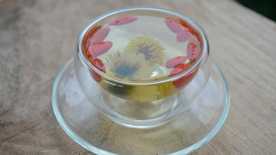 Clear cup with chrysanthemum and goji berry tea on wooden table