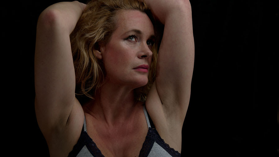 middle-aged blonde woman wearing grey bra with black lace lining holding her arms above her head exposing her armpits and looking sad