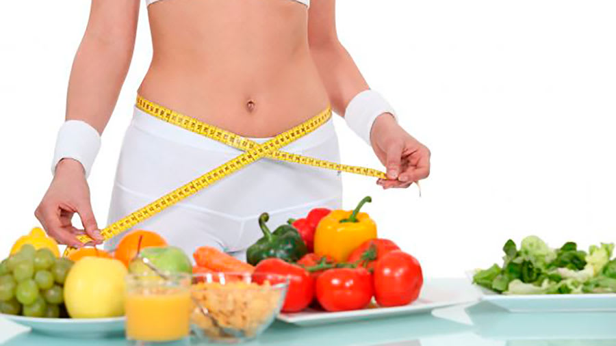 Fit woman measuring belly with tape measure with fruits, grains, vegetables, and juice on table