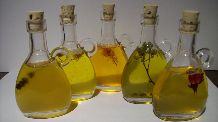 Multiple herbal oils arranged in glass containers with wooden corks