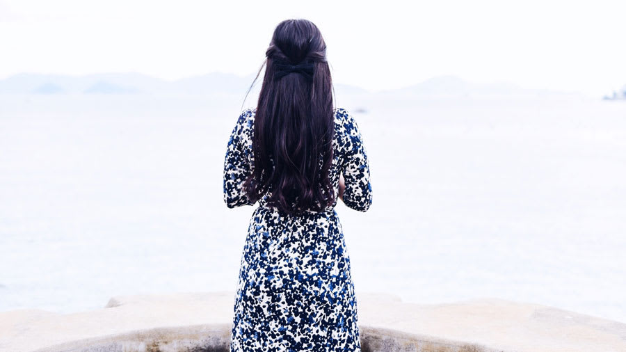 Woman with long black silky hair tied with a bow wearing a long blue and white floral dress