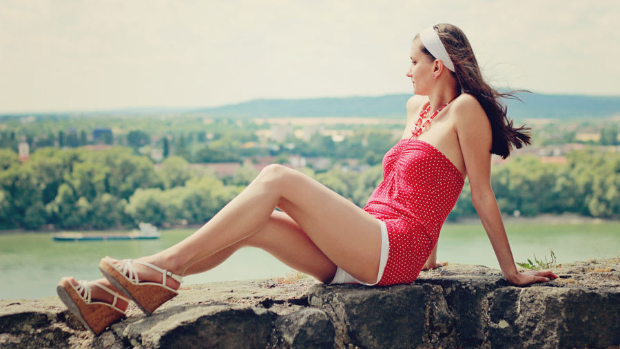 Beautiful woman in red dress on ledge with bare legs