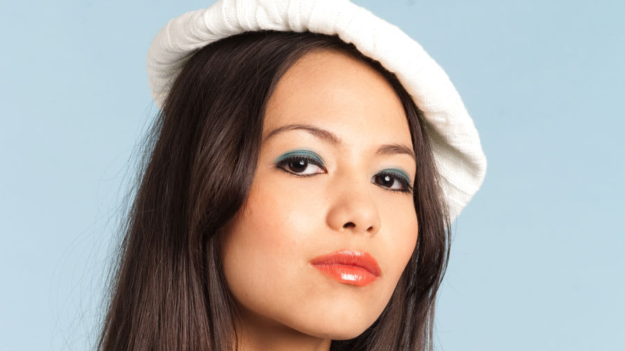 Face of asian woman with blue eyeshadow and white beret and necklace with a blue background