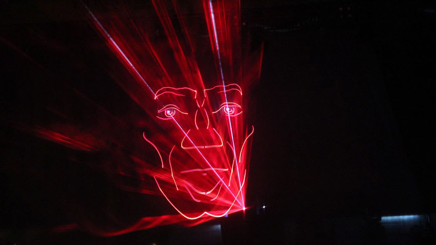Red lasers shining at night and making a human face pattern