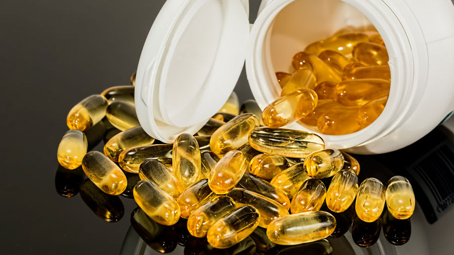 Yellow supplement capsules spilling out of white bottle
