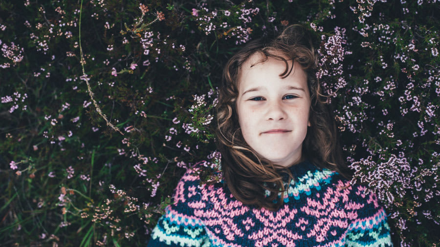 Girl in sweater lying on the ground surrounded by pink flowers
