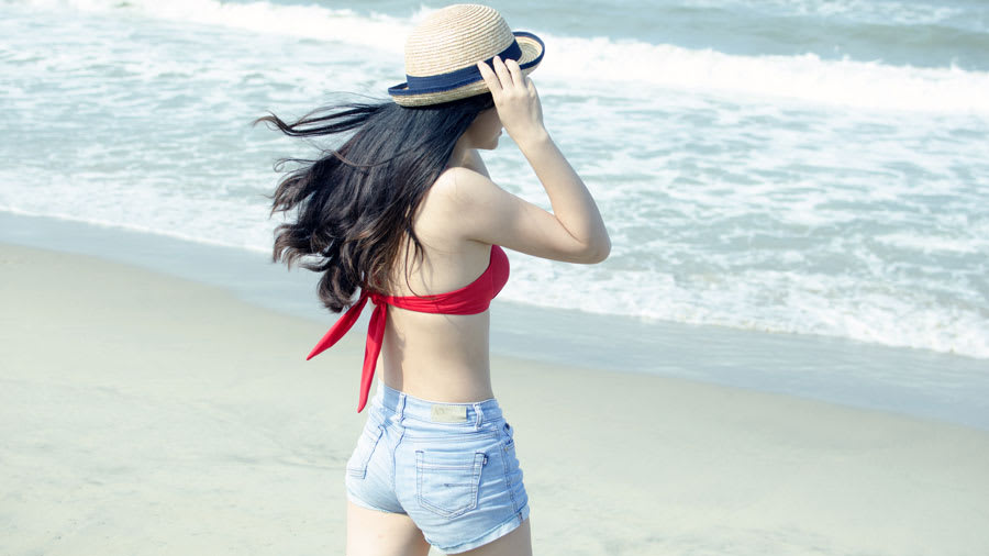 Young woman at beach with red bikini top jean shorts and white hat