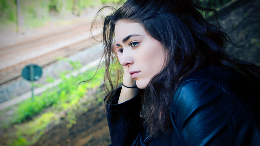 pretty girl with black hair dressed in black looking sad and thinking to herself