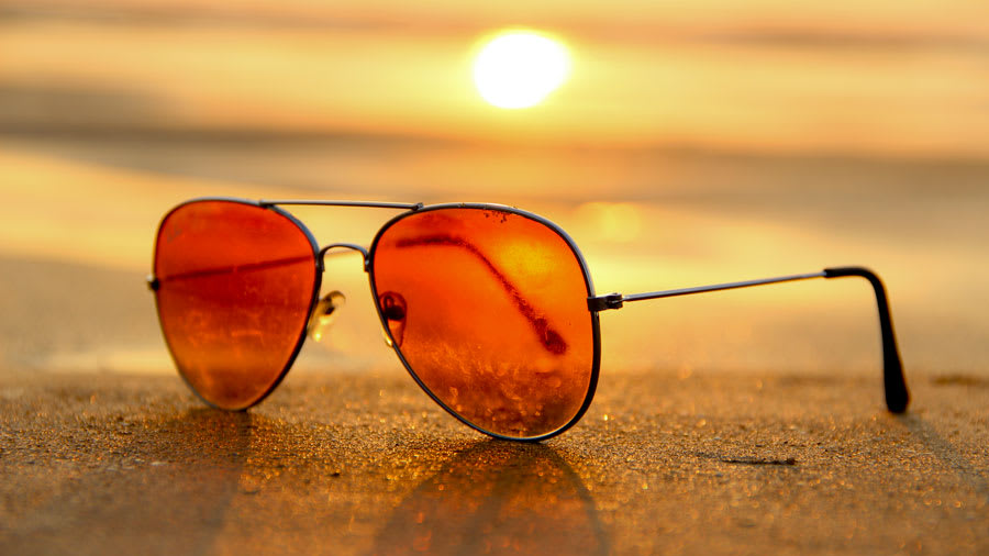 Rose colored sunglasses on the beach with sun setting in background