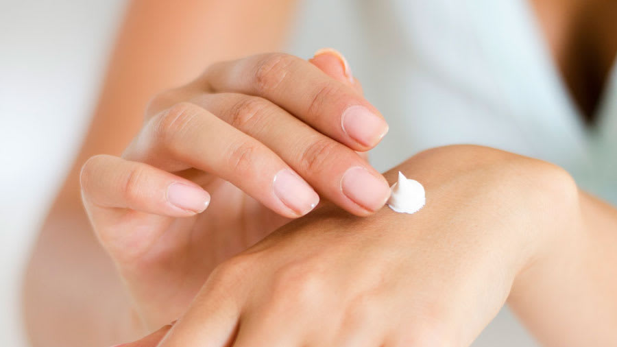 Woman rubbing a white cream onto her hand