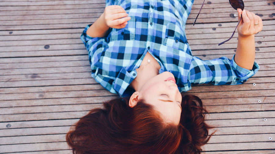 Woman in blue plaid shirt relaxing on deck lying down after cognitive behavioral therapy