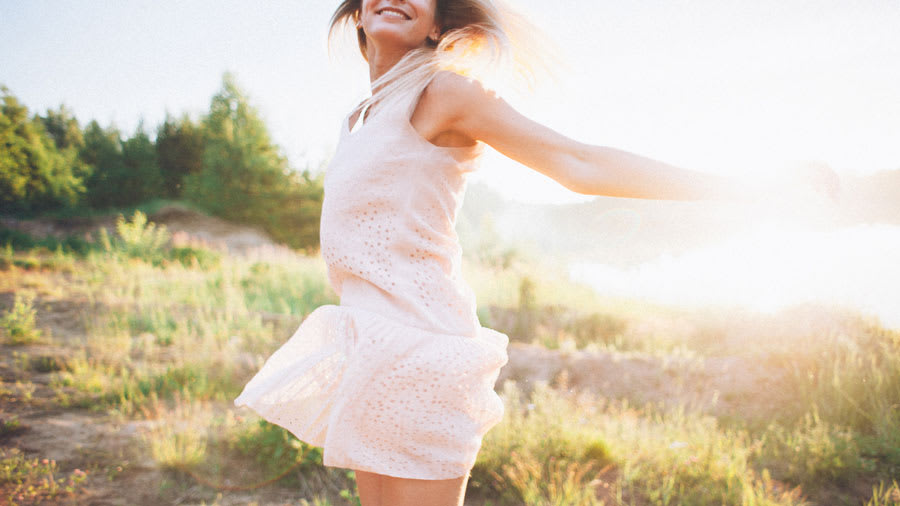 Woman wearing white dressing spinning outdoors with sun in background