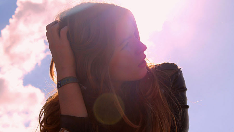 Beautiful woman looking to the side with sky and clouds in background and sunlight backlighting the face