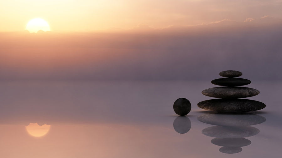 Stone balanced on motionless water with setting sun in background