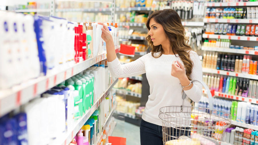beautiful young woman with long wavy brown hair wearing a white shirt and jeans shopping for perfect beauty product in story