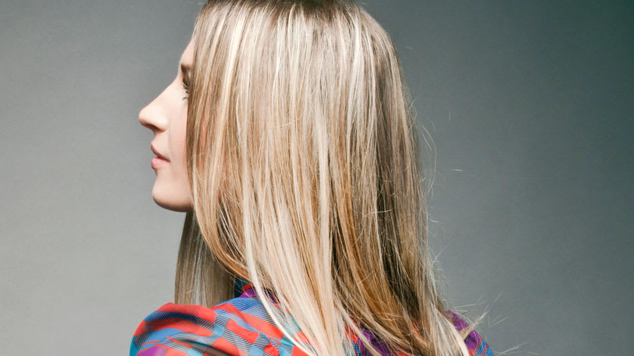 Woman with blonde hair and wearing plaid design shirt
