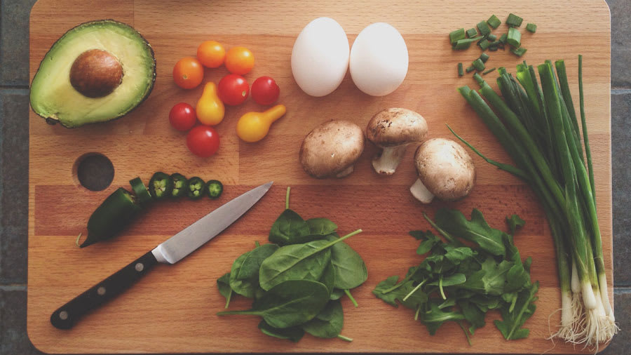 Avocado, spinach, mushrooms, tomatoes, onions, and a knife on a wooden cutting board