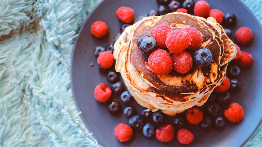 stack of pancakes with raspberries and blueberries on blue plate on blue carpet