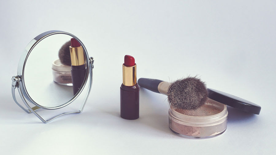 Mirror, red lipstick, and facial powder with brush