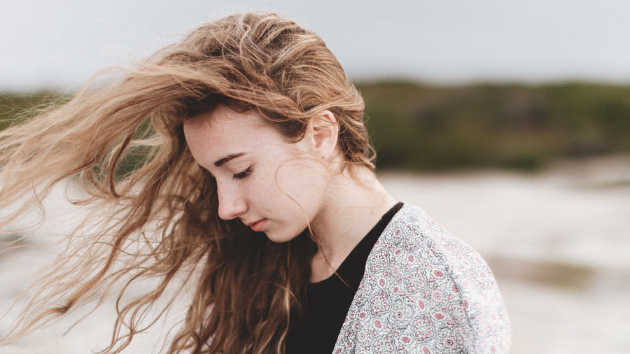 Woman on the beach in sweater with wind blowing her brown hair
