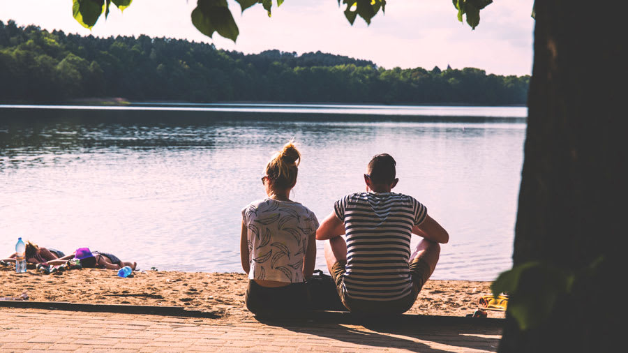Couple sitting in front of a lake next to a tree