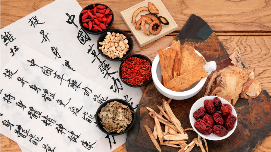 Chinese herbs on wooden table next to Chinese writing