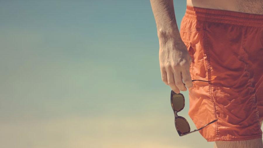 Man holding sunglasses wearing an orange swimsuit on beach
