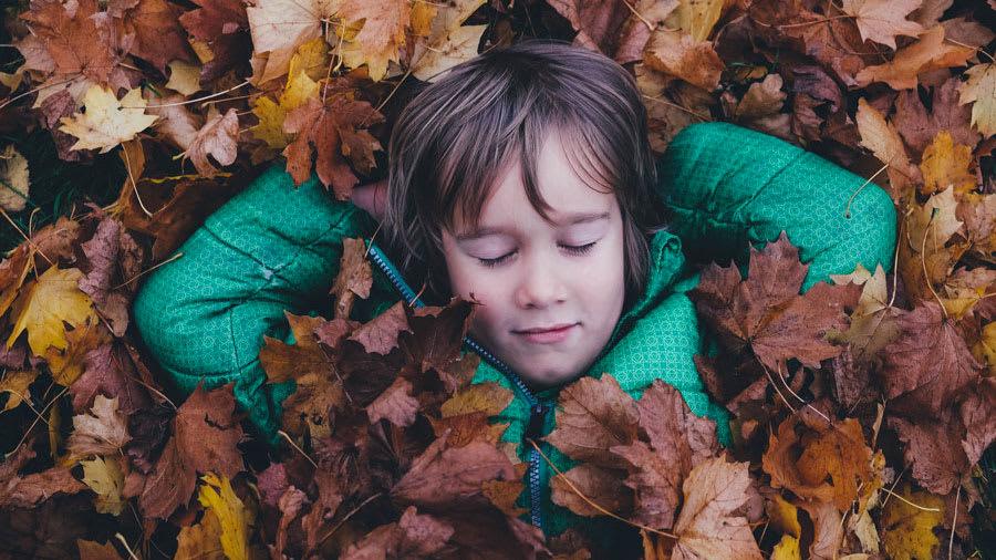 Boy in green jacket sleeping in fallen brown leaves