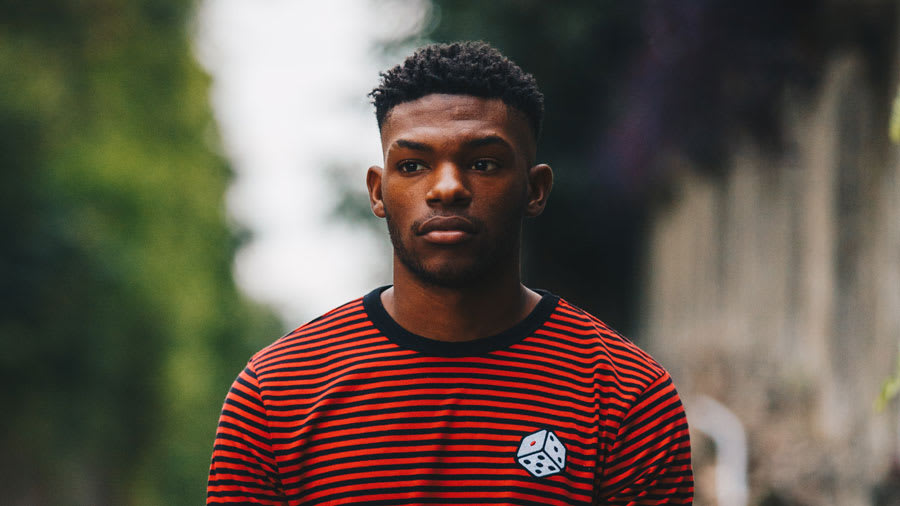 Young male in red and black striped shirt looking as if in deep thought with trees in background