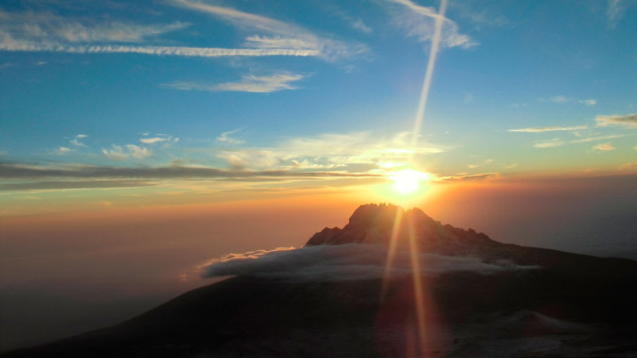 Sunrise over the horizon above mountains and clouds