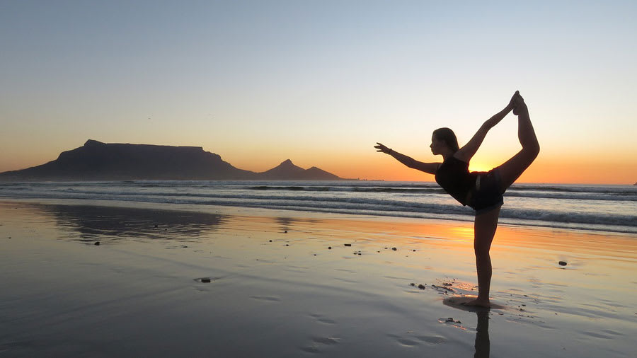 woman doing a yoga pose on beach shore during sunset