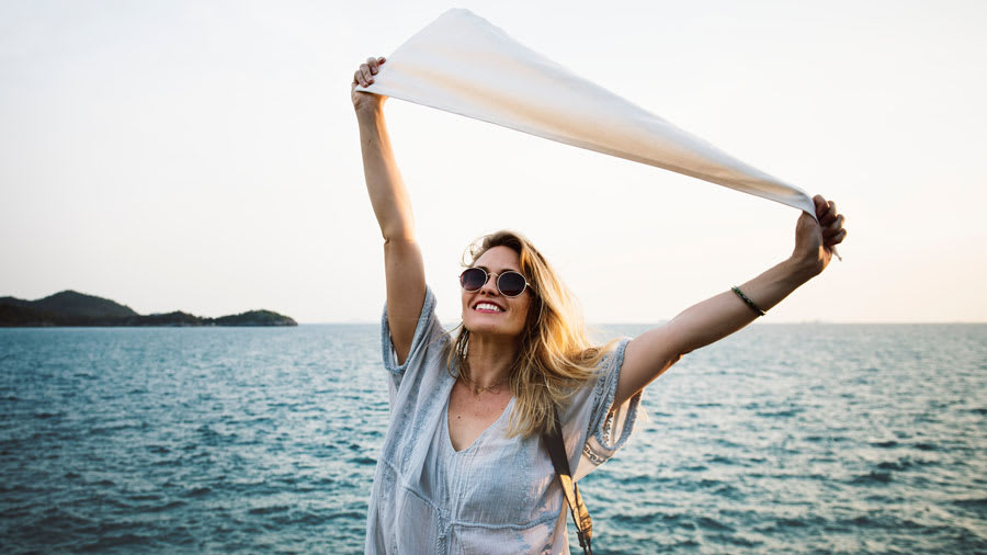 Woman in sunglasses raising arms in happiness in front of the ocean