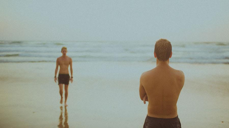 Men walking on the beach near the ocean