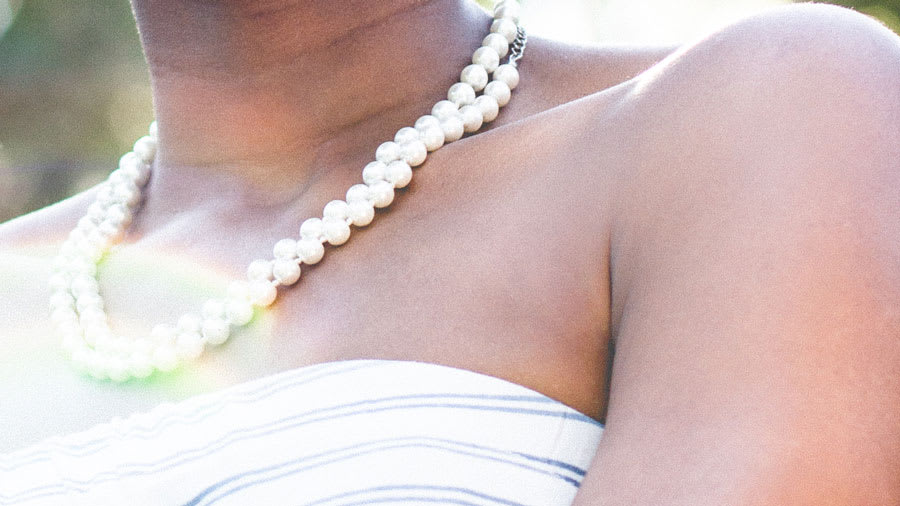 Young woman outside in pearls with glowing skin